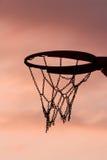 De hoepel van het basketbal in zonsondergang royalty-vrije stock afbeelding