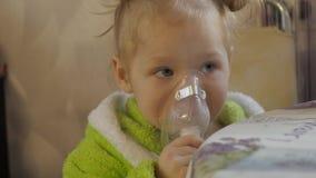 De hoestende baby wordt geïnhaleerd met verstuiver Het meisje wordt behandeld voor een koude 4K stock footage