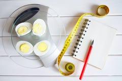 De hoeveelheid proteïne, calorieën, koolhydraten en vetten in voedsel Besnoeiingsei op de keukenschalen stock afbeeldingen