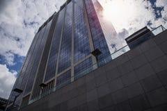 De hoge bedrijfsbouw in het centrum van de achtergrond van dramatische blauwe hemel Royalty-vrije Stock Foto