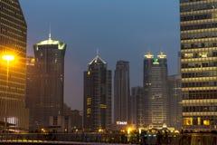 De hoge bouw met blauwe hemelachtergrond bij nacht stock fotografie