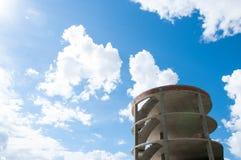 De hoge concrete bouw tegen de blauwe hemel en de witte wolken royalty-vrije stock fotografie