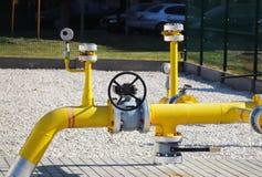 De hoge en middelgrote druk van de elementengasleiding Gele vervoerpijpen op de oppervlakte van de omheining Regelgevend levering royalty-vrije stock foto