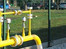 De hoge en middelgrote druk van de elementengasleiding Gele vervoerpijpen op de oppervlakte van de omheining Regelgevend levering stock foto's