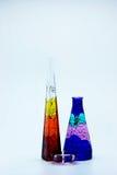 De hoge fles van het kleurenglas op witte achtergrond Stock Foto