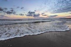 De hoge golven met schuim spreiden op het zand op de kust uit het licht van ongelooflijke zonsondergang het overzees overdenkt Be royalty-vrije stock fotografie