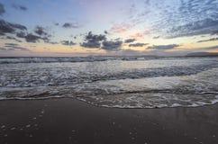 De hoge golven met schuim spreiden op het zand op de kust uit het licht van ongelooflijke zonsondergang het overzees overdenkt Pr stock afbeelding