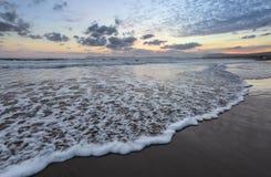 De hoge golven met schuim spreiden op het zand op de kust uit het licht van ongelooflijke zonsondergang het overzees overdenkt Pr royalty-vrije stock afbeeldingen