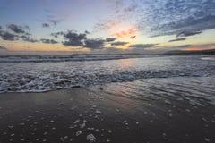 De hoge golven met schuim spreiden op het zand op de tijd van de kust Predageraad uit Het licht van ongelooflijke zonsondergang o royalty-vrije stock foto