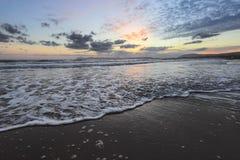 De hoge golven met schuim spreiden op het zand op de tijd van de kust Predageraad uit Het licht van ongelooflijke zonsondergang o royalty-vrije stock fotografie