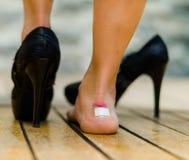 De hoge hielen kwetst zeer vaak, voeten met wit weinig flard op enkel, één voet op de vloer en andere met zwarte schoen Royalty-vrije Stock Afbeeldingen