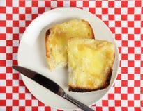 De hoge hoek van de toast met gesmolten kaas met mes Stock Foto's