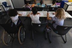 De hoge hoekmening van maakt schoolmeisje met klasgenoten onbruikbaar die en bij bureau in klaslokaal bestuderen zitten royalty-vrije stock afbeeldingen
