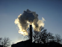 De hoge Schoorsteen zendt Rook tijdens Zonsondergang uit Royalty-vrije Stock Foto's