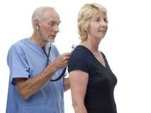 De hogere arts schrobt binnen met stethoscoop Stock Fotografie