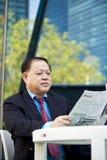 De hogere Aziatische krant van de zakenmanlezing stock afbeelding