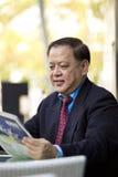 De hogere Aziatische krant van de zakenmanlezing stock fotografie
