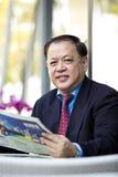 De hogere Aziatische krant van de zakenmanlezing stock afbeeldingen