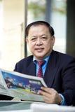 De hogere Aziatische krant van de zakenmanlezing stock foto's
