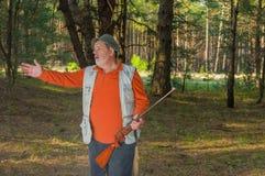 De hogere boswachter met geweer gesticuleert Stock Foto's