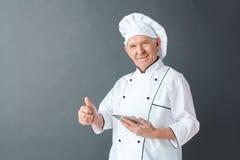 De hogere chef-kokstudio die zich op de grijze duim van de holdings digitale tablet omhoog bevinden stelde met toepassing tevrede royalty-vrije stock fotografie