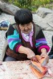 De hogere Chukchi-vrouw bereidt zalm voor royalty-vrije stock afbeeldingen