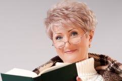 De hogere dame met een boek Stock Foto's