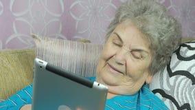 De hogere grootmoeder houdt binnen een tabletcomputer stock videobeelden