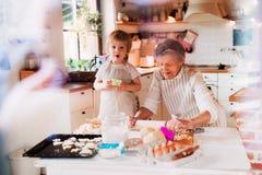 De hogere grootmoeder met het kleine peuterjongen maken koekt thuis stock afbeeldingen
