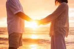 De hogere Handen die van de Paarholding bij Zonsondergang genieten van royalty-vrije stock afbeelding