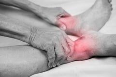 De hogere holding van de mensenhand hij gezonde voet en het masseren van enkel in p royalty-vrije stock afbeelding
