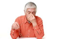 De hogere Japanse mens lijdt aan Asthenopia-hoofdpijn, vermoeide mens, geïsoleerde zieken, droevig beklemtoonde spanning, portret Royalty-vrije Stock Afbeelding