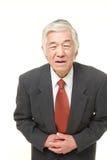 De hogere Japanse zakenman lijdt aan maagpijn stock foto
