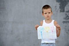 De hogere jongen in een grote familie gaat naar school en toont zijn tekeningen Stock Foto
