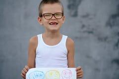 De hogere jongen in een grote familie gaat naar school en toont zijn tekeningen Royalty-vrije Stock Afbeeldingen