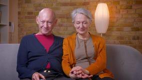 De hogere Kaukasische echtgenoten letten op komedie op TV lachend aan scheuren bij bank in woonkamer stock footage