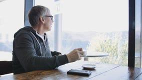 De hogere Kaukasische mens die van de sportstijl uit het venster de koffie bekijken Oude grijze mens die drinkend koffie bij de l stock footage