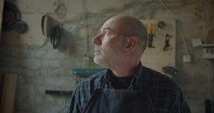 De hogere mannelijke timmerwerk hoofd status bij houten vervaardiging draait aan camera die ernstig en kalm zijn stock footage
