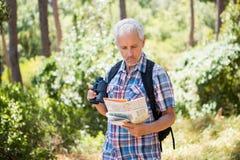 de hogere mens bevindt zich en draagt een kaart en verrekijkers Royalty-vrije Stock Foto's