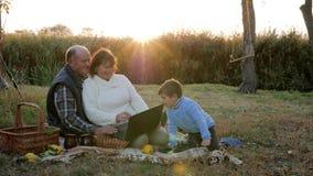 De hogere mens en zijn vrouw gebruiken laptop met kleinzoon bij picknick op achtergrond van zonsopgang stock video