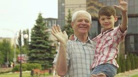 De hogere mens houdt zijn kleinzoon in zijn wapens stock afbeelding