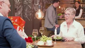 De hogere mens maakt tot een heden aan zijn vrouw op een verjaardag stock footage