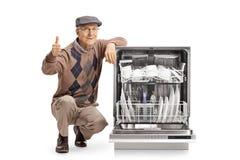 De hogere mens met afwasmachine het tonen beduimelt omhoog stock foto