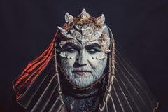 De hogere mens met witte baard kleedde zich als monster Fantasieconcept De mens met doornen of wratten, gezicht wordt behandeld d stock fotografie