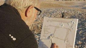 De hogere mens schildert een beeld op het strand Achtermening van bejaarde mannelijke kunstenaar die verf toepassen op canvas met stock videobeelden