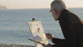 De hogere mens schildert een beeld op het strand Bejaarde mannelijke kunstenaar die verf verwijderen uit het palet en op canvas m stock video