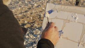 De hogere mens schildert een beeld op het strand Over de schouder van bejaarde mannelijke kunstenaar wordt geschoten die verfmeng stock video