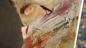 De hogere mens schildert een beeld op het strand Over het schouderclose-up van bejaarde mannelijke kunstenaar die in glazen verf  stock video