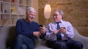 De hogere mens toont smartphone aan zijn vriend en zij worden opgewekt en blij stock video