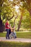 De hogere mens van de familietijd in rolstoel en dochter in het park Stock Foto's